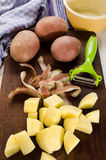 Potato cubes and vegetable peeler on a wooden board Stock Photo