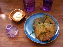 Potato flapjack draniki with sour cream and violet glass on wooden table. Potato flapjack draniki with sour cream and violet glass Stock Photos