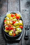 Potato with fresh tomato and garlic on barbecue dish Royalty Free Stock Images