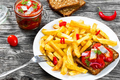 Potato Fries with pieces of chili pepper on the white dish and Slices of marinated Norwegian herring in tomato sauce on the pieces Royalty Free Stock Photos