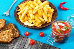 Potato Fries with pieces of chili pepper on the white dish and Slices of marinated Norwegian herring in tomato sauce on the pieces Royalty Free Stock Images