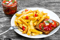 Potato Fries with pieces of chili pepper on the white dish and Slices of marinated Norwegian herring in tomato sauce on the pieces Stock Photos