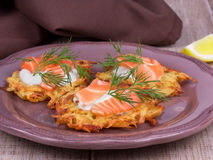 Potato fritters. Golden potato fritters with salmon served with creamy sauce Royalty Free Stock Photo