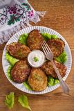 Potato fritters, latkes, draniki, hash browns - popular dish in many countries. Vegetable pancakes on white plate, wooden table. overhead, vertical royalty free stock image