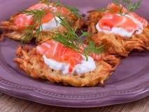 Potato fritters with salmon. Golden potato fritters with salmon served with creamy sauce Stock Photos