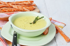 Potato and garlic cream soup with bread sticks Royalty Free Stock Images