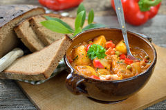 Potato goulash. Hot vegetarian potato goulash served in a ceramic bowl with delicious dark baked farmhouse bread on an old wooden table, a Tyrolean mountain Stock Image