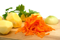 Potato and grated carrots on a chopping board Stock Images