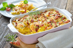 Potato gratin with bacon. Hearty potato gratin with parmesan cheese, cream and delicious cured bacon from South Tyrol freshly served from the oven Stock Photos