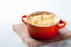 Potato gratin with bechamel. And cheese on orange cocotte stock photos