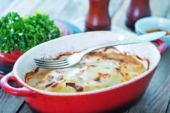 Potato gratin. In bowl and on a table royalty free stock photos