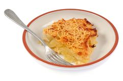 Part of gratin Dauphinois in a plate on a white background royalty free stock image