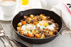 Potato hash with eggs. Potato and sweet potato hash with eggs in cast iron pan royalty free stock photos