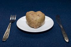 Potato Heart. Root of potato in the form of heart rests on a plate Royalty Free Stock Photography