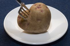Potato Heart. Root of potato in the form of heart rests on a plate Stock Photo