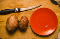 potato with knife and red plate  on a desk Stock Photos
