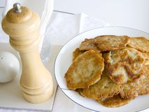 Potato latkes. A plate of potato latkes with pepper mill, salt shaker and napkins at a breakfast table Royalty Free Stock Photos