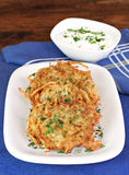 Potato Latkes and sour cream, vertical. Royalty Free Stock Images