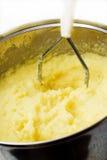 Potato mash with masher. Stock Image
