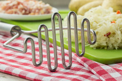 Potato masher and ingredients for typical dutch dish zuurkool Royalty Free Stock Images
