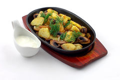 Potato with mushrooms. On a hot frying pan on a white background royalty free stock photo