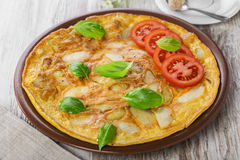 Potato omelette. With tomatoes on a plate stock images