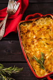 Potato-onion casserole. In a ceramic form with a sprig of rosemary on dark wooden background with red napkin and forks Stock Photos