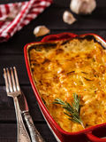 Potato-onion casserole. In a ceramic form with a sprig of rosemary on dark wooden background with red napkin and forks Stock Photo