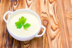 Potato and onion vegan, vegetarian healthy cream soup in white bowl. Tasty potato soup with a leaf of parsley, rustic wooden table. Potato and onion vegan stock photos