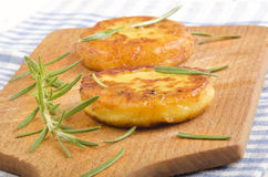 Potato pancake with rosemary on wooden board Royalty Free Stock Images
