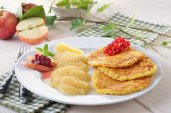 Potato pancakes. Baked potato pancakes with applesauce, cranberries and redcurrants Stock Photos