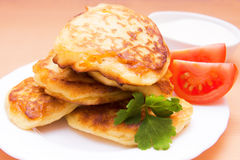 Potato pancakes. Fried potato pancakes on white plate with vegetable garnish and sour cream Royalty Free Stock Photo
