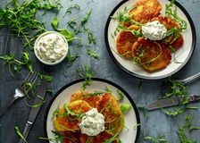 Potato pancakes, draniki, hash browns or fritters served with... fresh wild rocket leaves salad. Potato pancakes, draniki, hash browns or fritters served with Royalty Free Stock Photography
