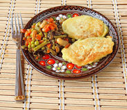 Potato pancakes with the extinguished green-stuffs. Lean potato pancakes with the extinguished green-stuffs on a decorative dish with the Ukrainian decorative stock image