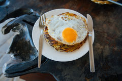 Potato pancakes with fried eggs are served with a knife and fork. On the oak table. Cafe by the sea. Stock Photos