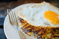 Potato pancakes with fried eggs are served with a knife and fork. On the oak table. Cafe by the sea. Stock Images