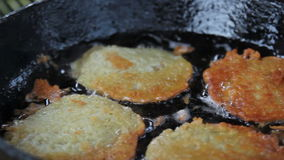 Potato pancakes fried in a pan with vegetable oil.