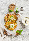 Potato pancakes or latkes with cream served on olive cutting Board over white wooden table. Rustic style. Stock Images