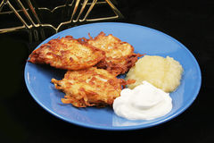 Potato Pancakes - Latkes For Hanukkah. A plate of delicious potato pancakes, or latkes for Hanukkah, with the traditional garnish of sour cream and applesauce