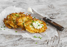 Potato pancakes or latkes on a light rustic wood surface Stock Photos