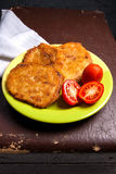 Potato pancakes with meat and tomatoes on green plate in Belarus Stock Image