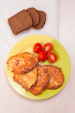 Potato pancakes with meat and tomatoes on green plate with rye b Stock Photos
