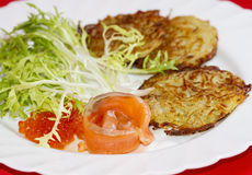 Potato pancakes with a piece of salmon and red caviar Stock Image