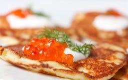 Potato pancakes with red caviar Stock Images
