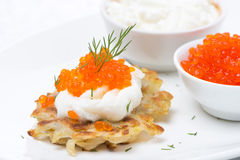 Potato pancakes with red caviar and sour cream, close-up Stock Photo