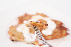 Potato Pancakes. With some cream and brown sugar being eaten with a fork Stock Image