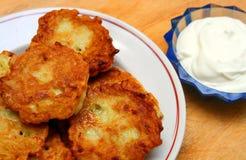 Potato pancakes with sour cream. Potato pancakes on plate with sour cream Stock Photos