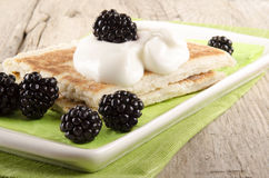 Potato pancakes with sour cream and blackberries Royalty Free Stock Image