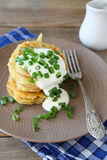 Potato pancakes with sour cream and green onions on a plate Royalty Free Stock Images