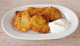 Potato pancakes with sour cream on a plate Stock Photo